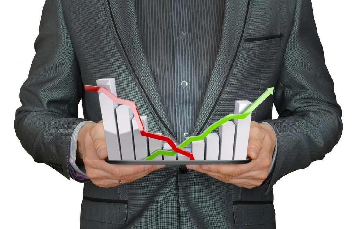 Guy in suit holding financial graph